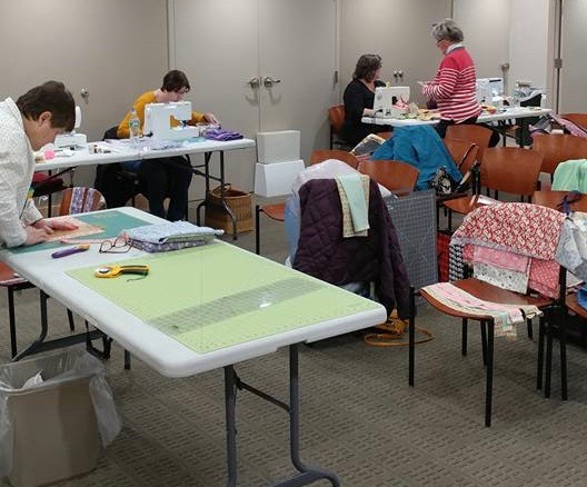Guild members working on charity quilts at a sew day
